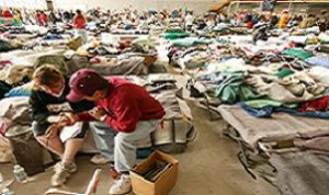 10-31-03 San Bernardino, California Reverend Misael prays with shelteree Jeri Wilde in evacuation shelter at Norton Air Force Base. Hanger 3 housed over 3000 evacuees following the fires in Southern California. Photo by Andrea Booher/FEMA No Payment/Mandatory credit